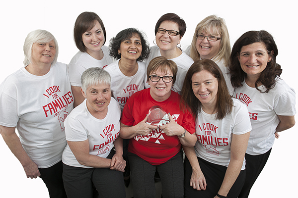 Deb Moniz's Fanshawe dinner group wearing their I Cook for Families T-Shirts