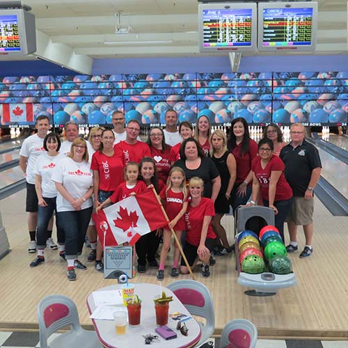 Large group of bowlers standing by bowling lanes holding the Canadian flag