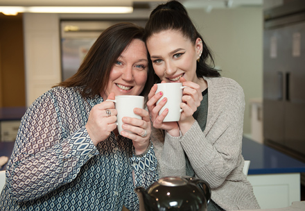 Emma and her mom hold white coffee mugs in RMH London Kitchen