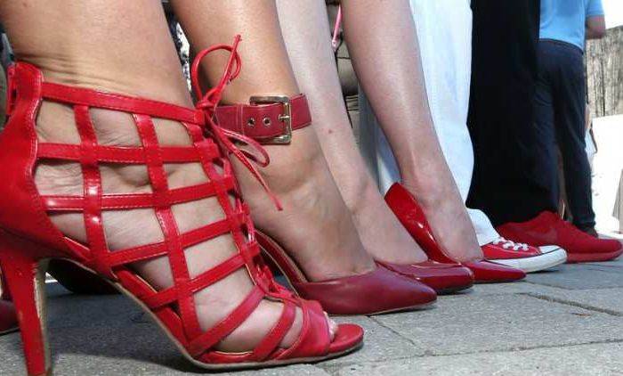 A row of feet sporting red shoes