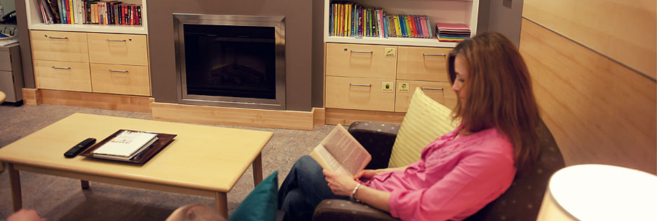 Female caregiver sitting on chair in RM Family Room London, taking a break and reading a book