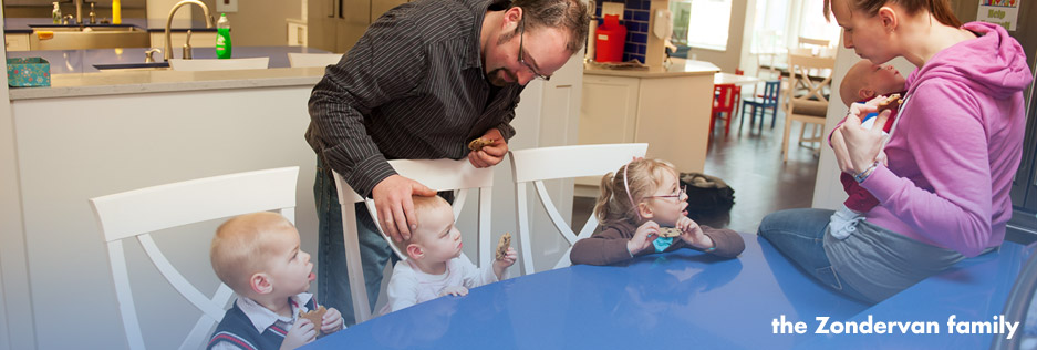 RMHC Southwestern Ontario guest family, the Zondervans, sit at RMH London's kitchen table while eating homemade cookies